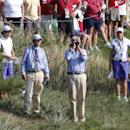 An official, center, uses a laser distance finder to measure the distance to the hole after Europe's Carlota Ciganda, left, of Spain, lost a ball on the 15th hole during four-ball matches at the Solheim Cup golf tournament, Friday, Aug. 16, 2013, in Parker, Colo. (AP Photo/Ed Andrieski)