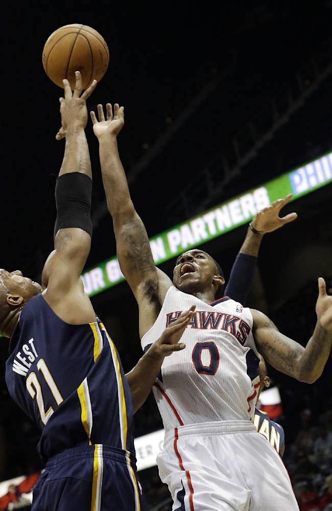 Atlanta Hawks point guard Jeff Teague (0) has his shot blocked by Indiana Pacers power forward David West (21) in the second half of a preseason NBA basketball game Tuesday, Oct. 22, 2013, in  Atlanta
