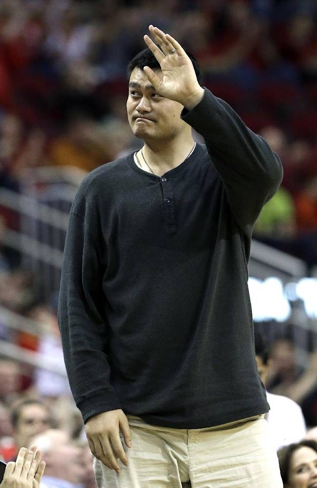 Former Houston Rockets Yao Ming waves to the crowd in the first half of an NBA basketball game between the Rockets and the Denver Nuggets Saturday, Nov. 16, 2013, in Houston