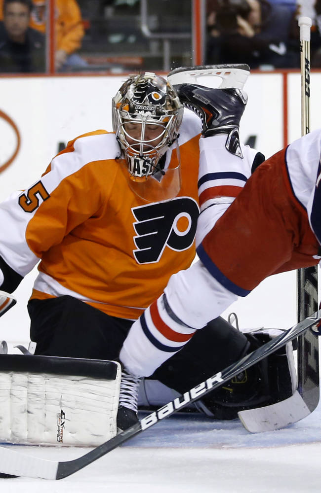 Columbus Blue Jackets' Nick Foligno, right, tries to get a shot past Philadelphia Flyers' Steve Mason during the first period of an NHL hockey game, Thursday, April 3, 2014, in Philadelphia