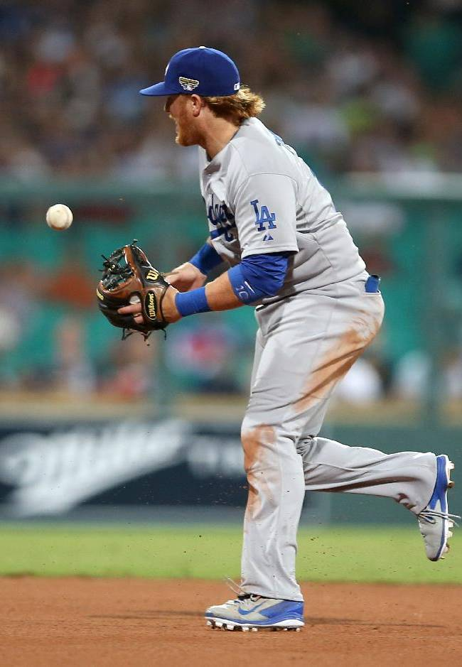 The Los Angeles Dodgers' Justin Turner bobbles the ball during the Major League Baseball opening game between the Los Angeles Dodgers and Arizona Diamondbacks at the Sydney Cricket ground in Sydney, Saturday, March 22, 2014