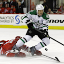 Dallas Stars' Cody Eakin (20) controls the puck as Carolina Hurricanes' Brett Bellemore falls to the ice during the first period of an NHL hockey game in Raleigh, N.C., Thursday, April 3, 2014 The Associated Press