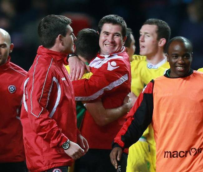 Sheffield United manager Nigel Clough, center, hugs Ryan Flynn after their FA Cup third round soccer match against Aston Villa at Villa Park, Birmingham, England, Saturday, Jan. 4, 2014