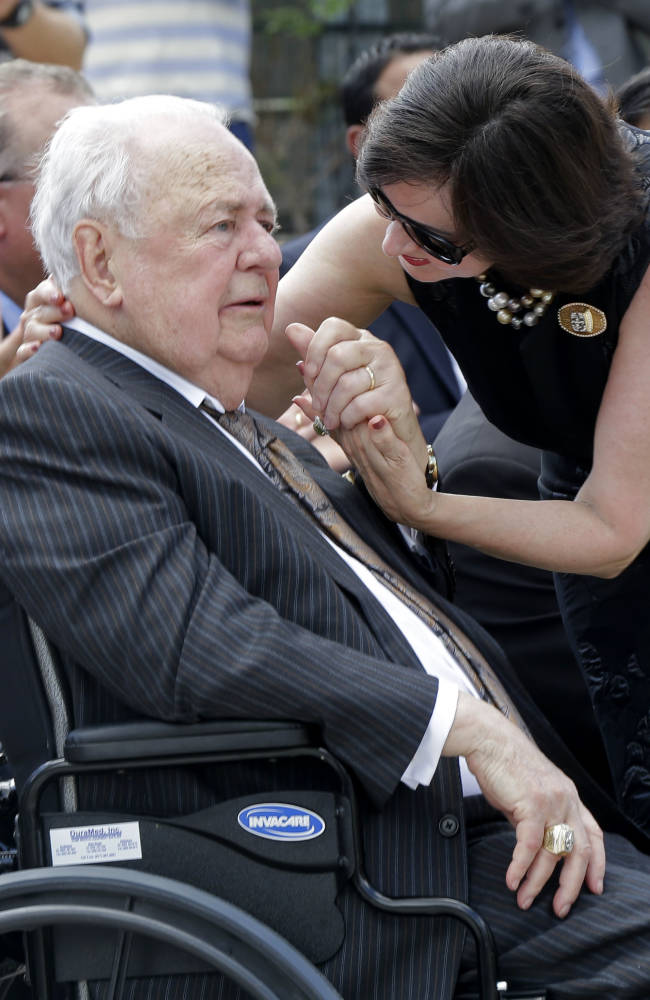New Orleans Saints owner Tom Benson reacts as his wife Gayle Benson holds his hand at the unveiling of a statue of him outside the Mecedes-Benz Superdome in New Orleans, Tuesday, Sept. 2, 2014