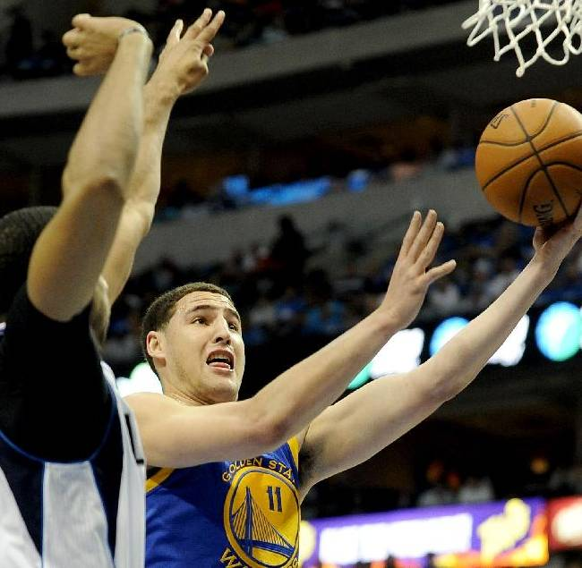 Golden State Warriors guard Klay Thompson (11) drives to the basket on Dallas Mavericks forward Brandan Wright (34) in the first half of an NBA basketball game, Tuesday, April 1, 2014, in Dallas