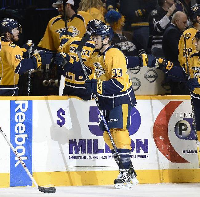 Nashville Predators forward Colin Wilson (33) is congratulated by his teammates after scoring a goal against the Detroit Red Wings in the first period of an NHL hockey game on Monday, Dec. 30, 2013, in Nashville, Tenn