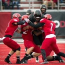 Montana Western running back Sam Rutherford is tackled by, left to right, Eastern Washington's Jake Hoffman, Todd Raynes, Tevin McDonald (7) during the first half of an NCAA college football game, Saturday, Aug. 30, 2014, in Cheney, Wash The Associated Pr