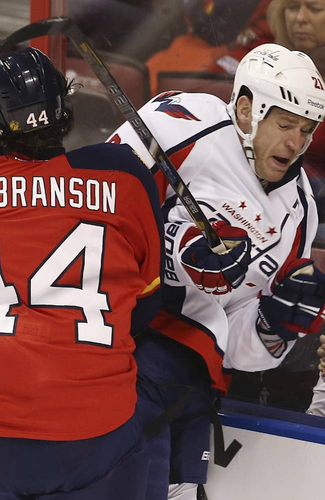 Florida Panthers' Erik Gudbranson (44) checks Washington Capitals' Brooks Laich (21) into the glass during the first period of an NHL hockey game, Thursday, Feb. 27, 2014, in Sunrise, Fla