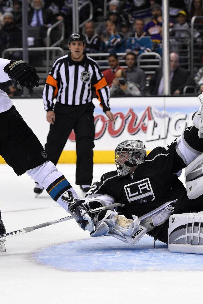 Los Angeles Kings goalie Jonathan Quick, right, tangles with San Jose Sharks center Logan Couture during the third period in Game 3 of an NHL hockey first-round playoff series, Tuesday, April 22, 2014, in Los Angeles