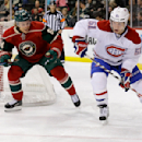 Montreal Canadiens center David Desharnais (51) controls the puck in front of Minnesota Wild center Mikael Granlund, center, of Finland, and Wild goalie Darcy Kuemper, left, during the second period of an NHL hockey game in St. Paul, Minn., Wednesday, De