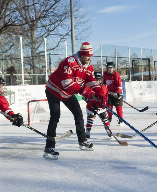 Detroit Red Wings' Niklas Kronwal, center left,  puts on a hockey clinic as part of the event at Clark Park in Detroit, Monday, Dec. 16, 2013.  The NHL and the Red Wings unveiled a