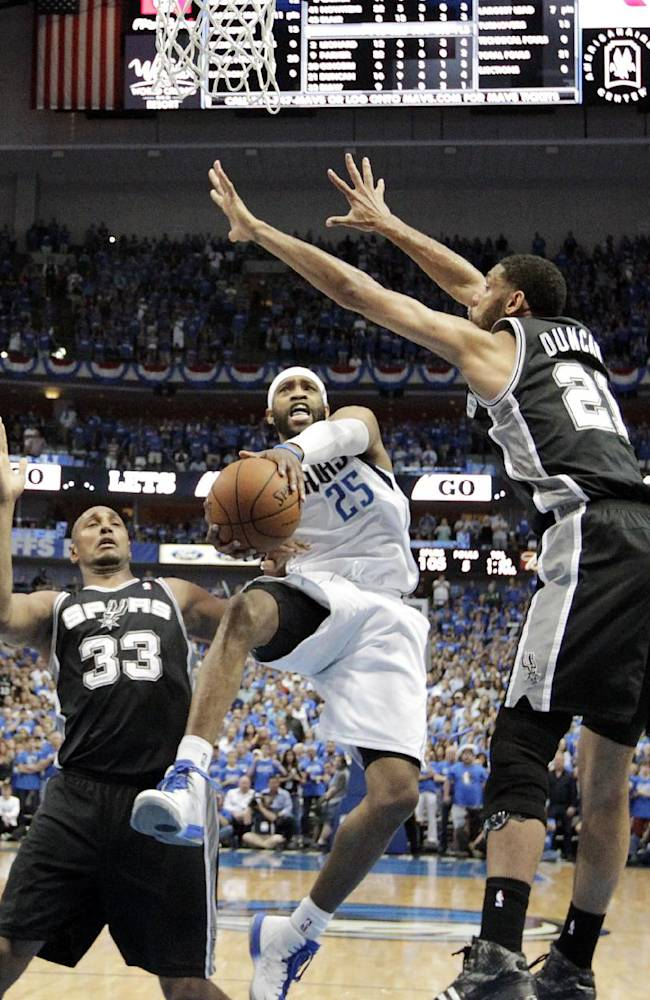Dallas Mavericks' Vince Carter (25) goes up for a shot as San Antonio Spurs' Boris Diaw (33) of France and Tim Duncan (21) defend in the second half of Game 6 of an NBA basketball first-round playoff series, Friday, May 2, 2014, in Dallas. The Mavericks won 113-111