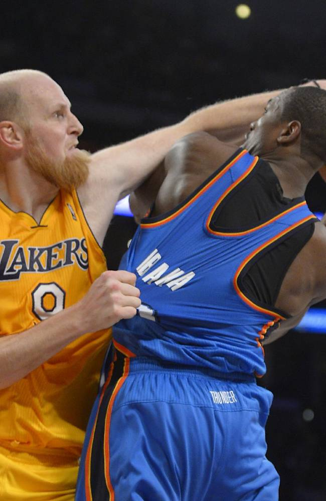 Los Angeles Lakers center Chris Kaman, left, fouls Oklahoma City Thunder power forward Serge Ibaka, of Congo, during the second half of an NBA basketball game, Thursday, Feb. 13, 2014, in Los Angeles