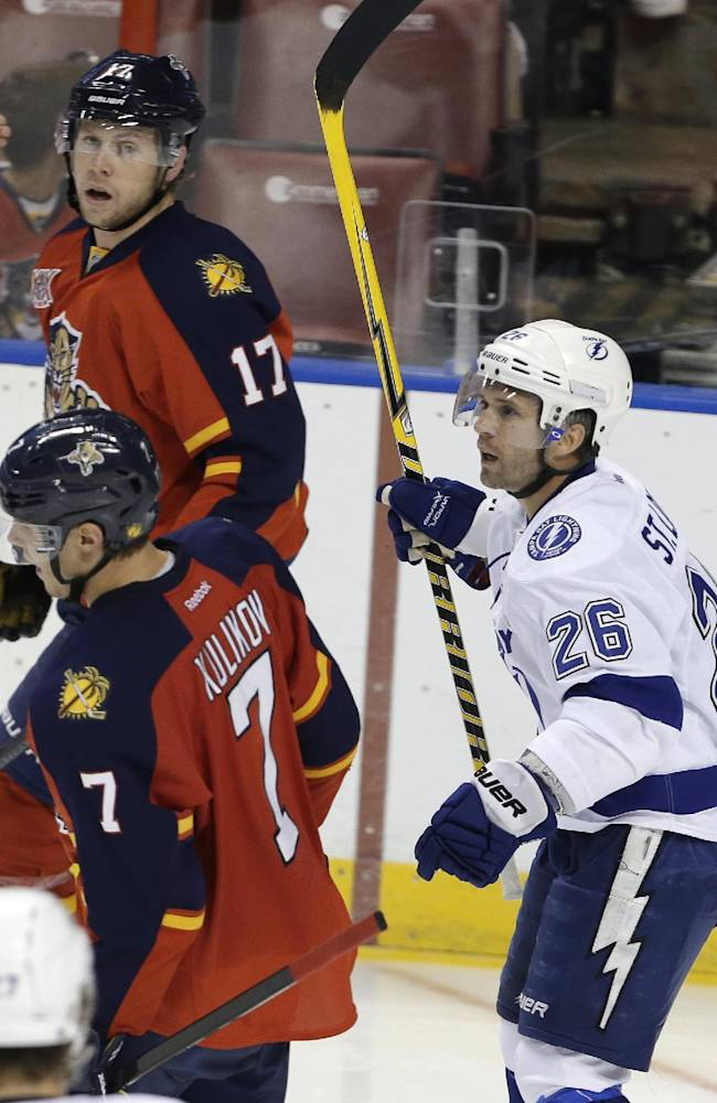 Tampa Bay Lightning right wing Martin St. Louis (26) raises his stick after scoring a goal in the third period during a preseason NHL hockey game against the Florida Panthers, Saturday, Sept. 28, 2013, in Sunrise, Fla. At left are Panthers center Jesse Winchester (17) and defenseman Dmitry Kulikov (7). The Panthers defeated the Lightning 5-3