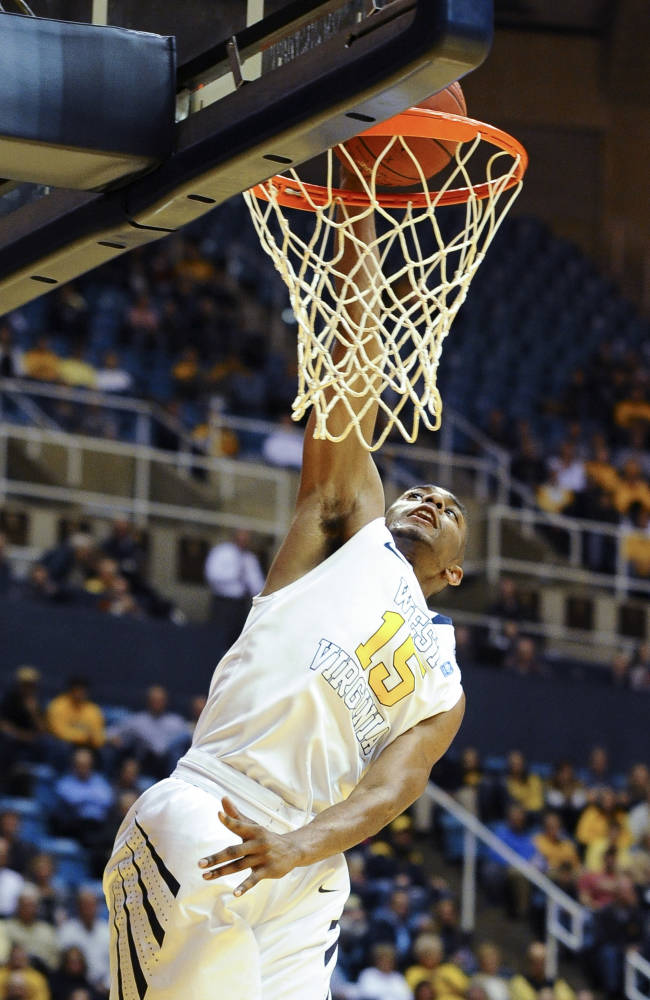 West Virginia's Terry Henderson (15) dunks during the second half of an NCAA college basketball game against Loyola Maryland, Monday, Dec. 2, 2013, in Morgantown, W.Va. West Virginia won 96-47