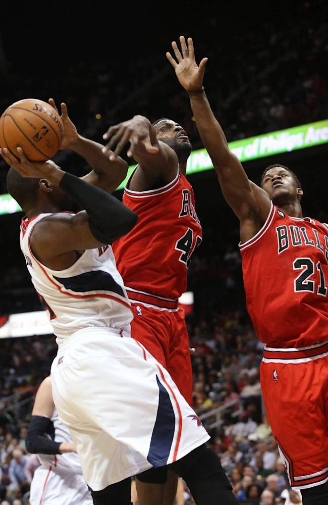 Atlanta Hawks forward Paul Millsap (4) attempts a shot as Chicago Bulls center Nazr Mohammed (48) and guard Jimmy Butler (21) defend during the first half of an NBA basketball game Wednesday, April 2, 2014, in Atlanta