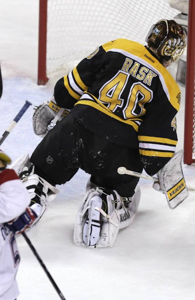 Boston Bruins goalie Tuukka Rask (40) flicks the puck away as Montreal Canadiens left wing Max Pacioretty (67) is congratulated on his goal during the second period in Game 7 of a second-round NHL hockey Stanley Cup playoff series in Boston, Wednesday, May 14, 2014. (AP Photo)