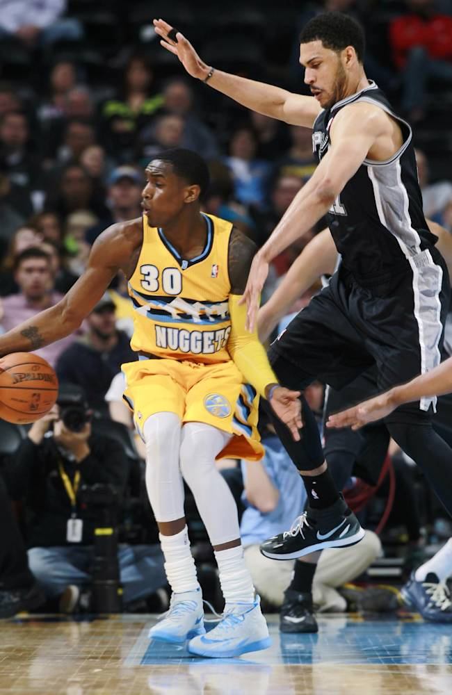 Denver Nuggets forward Quincy Miller, left, picks up loose ball as San Antonio Spurs forward Jeff Ayers defends in the fourth quarter of the Spurs' 133-102 victory in an NBA basketball game in Denver on Friday, March 28, 2014