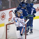 The Vancouver Canucks celebrate a goal by Daniel Sedin (obscured) as Edmonton Oilers goalie Viktor Fasth (35) looks on during the first period of an NHL hockey game in Vancouver, British Columbia, Saturday, Oct. 11, 2014 The Associated Press