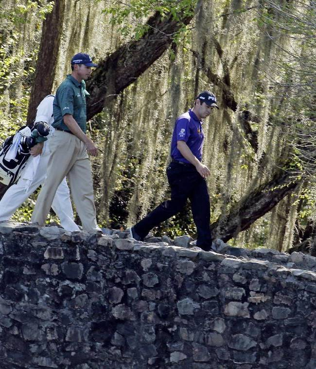 Louis Oosthuizen, right, of South Africa, and Matt Kuchar walk across the Byron Nelson Bridge during the first round of the Masters golf tournament Thursday, April 10, 2014, in Augusta, Ga