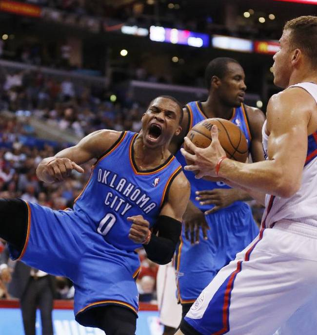 Oklahoma City Thunder guard Russell Westbrook, left, celebrates after dunking the ball over Los Angeles Clippers forward Blake Griffin, right, during the second half of an NBA basketball game in Los Angeles, Wednesday, April 9, 2014. The Thunder won 107-101
