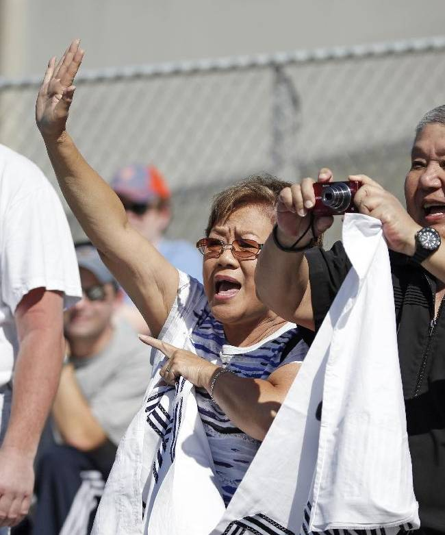 A woman calls out for her husband, right, to take a photo of Derek Jeter during batting practice before a spring training baseball game between the New York Yankees and the Tampa Bay Rays in Tampa, Fla., Sunday, March 9, 2014