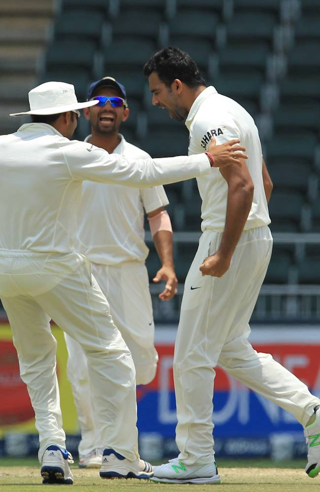 India's bowler Zaheer Khan, right, celebrates with teammates Ajinkya Rahane, center, and Rohit Sharma, left, after taking his 300 career wickets during the fourth and final day of their cricket test match against South Africa at Wanderers stadium in Johannesburg, South Africa, Sunday, Dec. 22, 2013