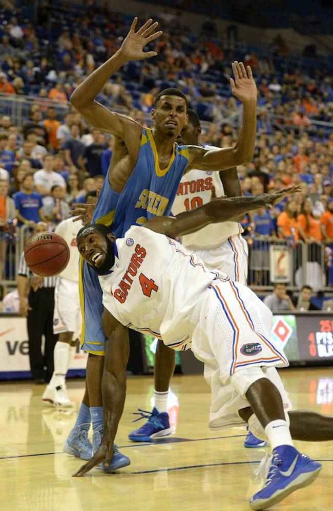 Florida center Patric Young (4) goes down with Southern University guard Malcolm Miller (33) staying out of the action during the  first half of an NCAA college basketball game Monday, Nov. 18, 2013 in Gainesville, Fla