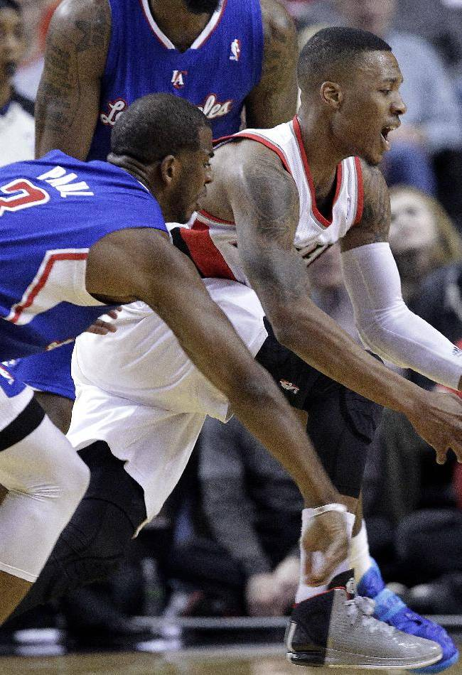 Portland Trail Blazers guard Damian Lillard, right, loses control of the ball as Los Angeles Clippers guard Chris Paul defends during the first half of an NBA basketball game in Portland, Ore., Thursday, Dec. 26, 2013