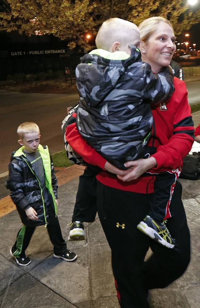 Maryland coach Brenda Frese carries one of her twin sons, Tyler, 6, as his brother, Markus, left, follows as the team arrives for the NCAA women's Final Four college basketball tournament Thursday, April 3, 2014, in Nashville, Tenn. Maryland is scheduled to play Notre Dame in a semifinal on Sunday