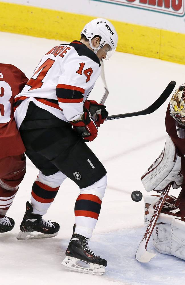Phoenix Coyotes' Mike Smith (41) makes a save on a shot by New Jersey Devils' Adam Henrique (14) as Coyotes' Derek Morris (53) also defends in front of the goal during the second period of an NHL hockey game on Saturday, Jan. 18, 2014, in Glendale, Ariz