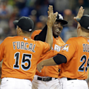 Miami Marlins' Marcell Ozuna, center, celebrates with Rafael Furcal (15) and Greg Dobbs (29) after the Marlins defeated the Colorado Rockies 10-1 in an opening day baseball game, Monday, March 31, 2014, in Miami The Associated Press