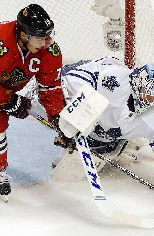 Chicago Blackhawks center Jonathan Toews (19) and Toronto Maple Leafs goalie Jonathan Bernier (45) vie in front of the goal during the second period of an NHL hockey game Saturday, Oct. 19, 2013, in Chicago