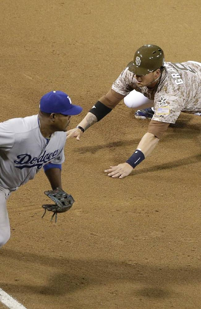 San Diego Padres' Yasmani Grandal, right, safely steals third base as Los Angeles Dodgers third baseman Juan Uribe moves off the base during the eighth inning during an opening night baseball game on Sunday, March 30, 2014, in San Diego