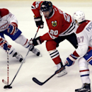 Chicago Blackhawks left wing Brandon Saad (20) controls the puck against Montreal Canadiens center David Desharnais (51) and left wing Max Pacioretty (67) during the third period of an NHL hockey game in Chicago, Friday, Dec. 5, 2014. The Blackhawks won 4