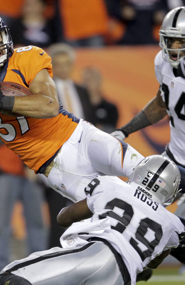 Denver Broncos wide receiver Eric Decker (87) is tackled by Oakland Raiders cornerback Brandian Ross (29) after gaining a first down in the second quarter of an NFL football game, Monday, Sept. 23, 2013, in Denver