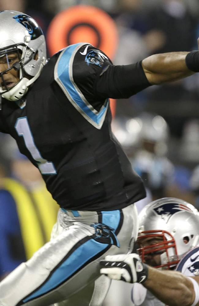 Carolina Panthers' Cam Newton (1) avoids a sack by a New England Patriots defender during the second half of an NFL football game in Charlotte, N.C., Monday, Nov. 18, 2013