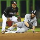 After tagging out Seattle Mariners' Dustin Ackley, right, Miami Marlins' Donovan Solano waits to if he got a double play during the sixth inning of a baseball game in Miami, Saturday, April 19, 2014. Solano got the double play The Associated Press