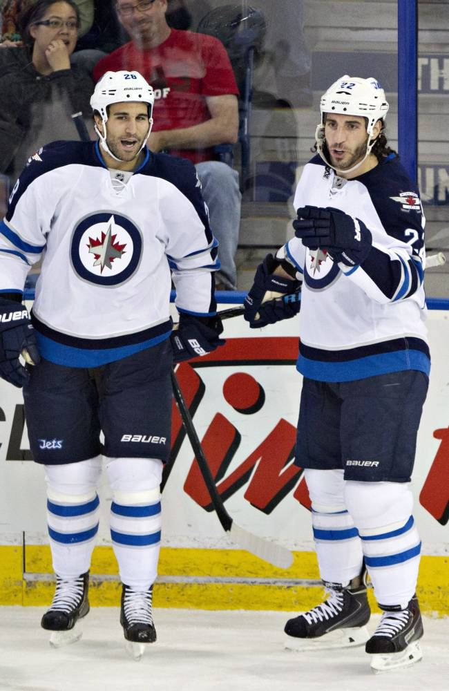 Winnipeg Jets' Blake Wheeler, left, and Chris Thorburn (22) celebrate a goal against the Edmonton Oilers during the first period of an NHL hockey preseason game Monday, Sept. 23, 2013, in Edmonton, Alberta