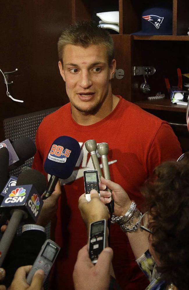 New England Patriots tight end Rob Gronkowski speaks with reporters during a media availability in front of his locker at the team's NFL football training facility in Foxborough, Mass.,Wednesday, Sept. 18, 2013