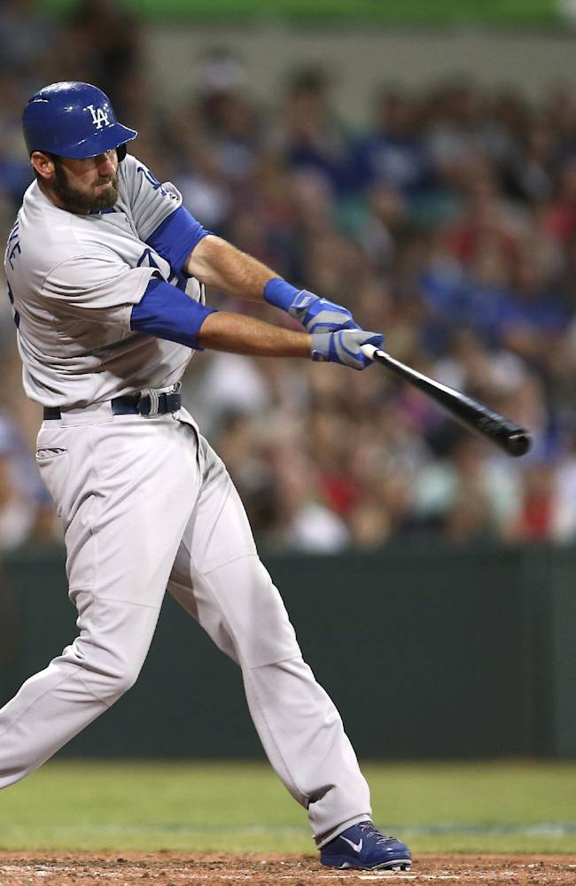 The Los Angeles Dodgers' Scott Van Slyke hits a two-run home run in the Major League Baseball opening game between the Los Angeles Dodgers and Arizona Diamondbacks at the Sydney Cricket ground in Sydney, Saturday, March 22, 2014