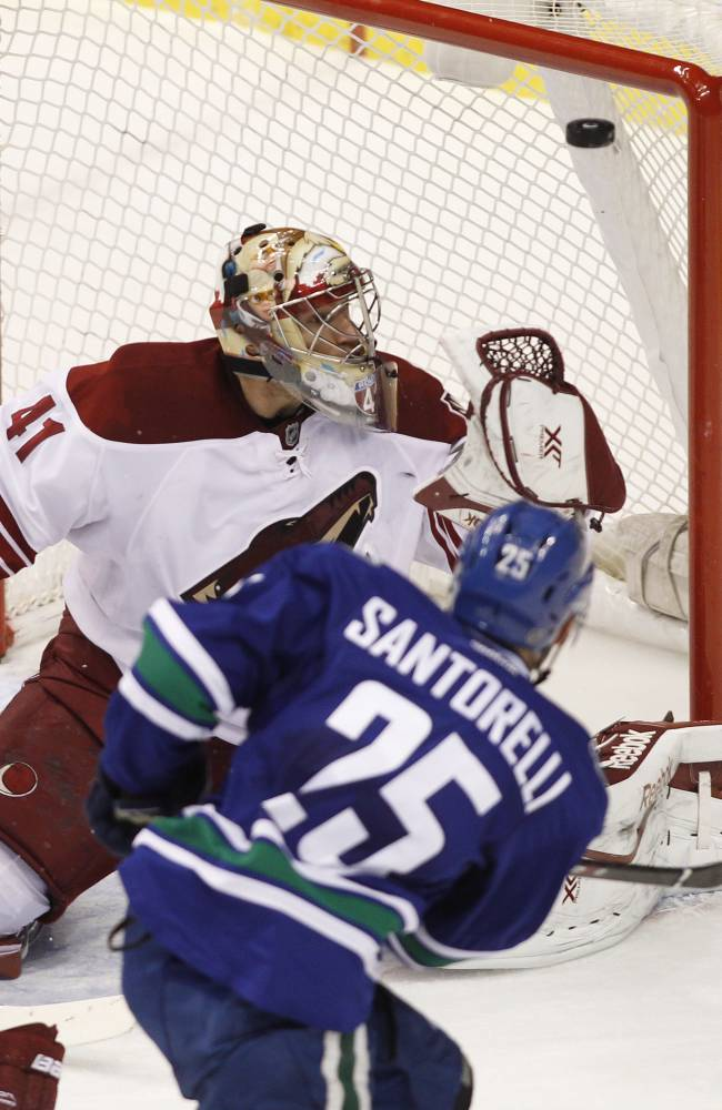 Phoenix Coyotes goaltender Mike Smith (41) makes a save against Vancouver Canucks' Mike Santorelli (25) during second period NHL hockey action in Vancouver, British Columbia, on Friday Dec. 6, 2013