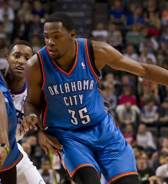 Oklahoma City Thunder's Kevin Durant, right, keeps the ball from Philadelphia 76ers' Thaddeus Young, left, as Evan Turner, centre left, looks on during their NBA preseason basketball game at the Phones4 u Arena in Manchester, England, Tuesday, Oct. 8, 2013