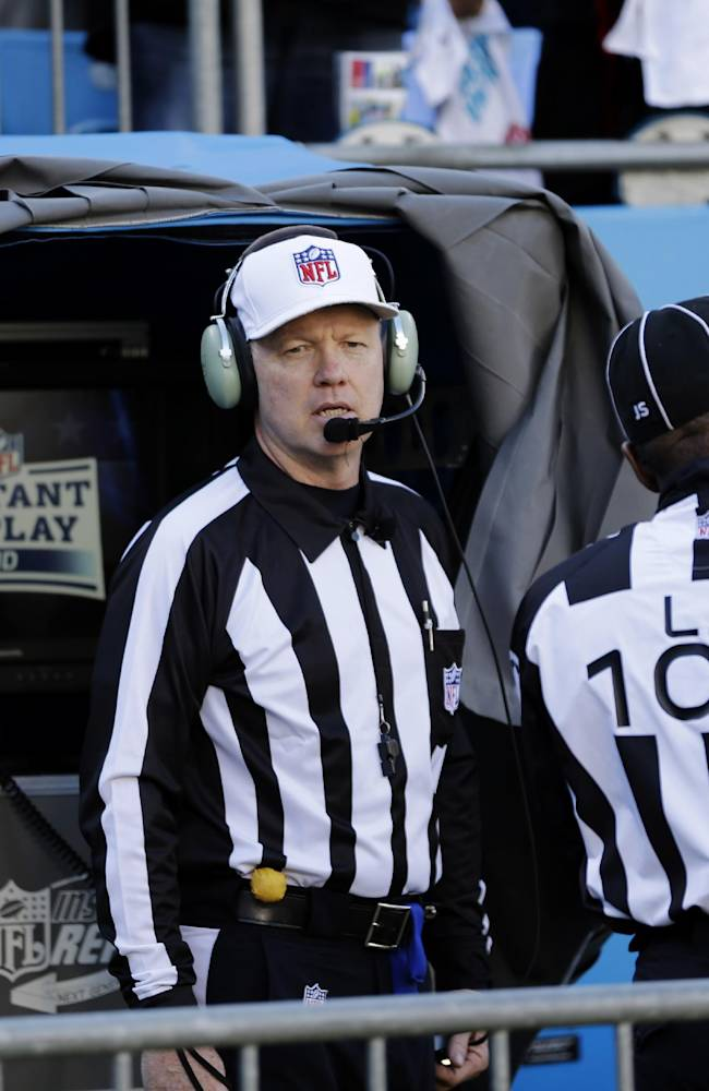 Officials watch an instant replay after a San Francisco 49ers touchdown against the Carolina Panthers during the first half of a divisional playoff NFL football game, Sunday, Jan. 12, 2014, in Charlotte, N.C
