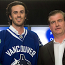Vancouver Canucks' goalie Ryan Miller, left, stands for photos with general manager Jim Benning after Miller signed a three-year contract with the NHL hockey team, Tuesday, July 1, 2014 in Vancouver, British Columbia The Associated Press