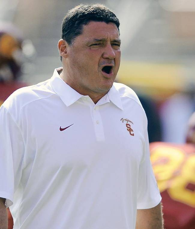 In this Oct. 26, 2013, file photo, Southern California head coach Ed Orgeron watches his players warm up before the start of an NCAA college football game against Utah in Los Angeles. Orgeron has refused to campaign for the permanent job while he orchestrates 23rd-ranked USC's remarkable midseason turnaround. But Trojans past and present are speaking up for the homespun coach who is 6-1 since replacing Lane Kiffin