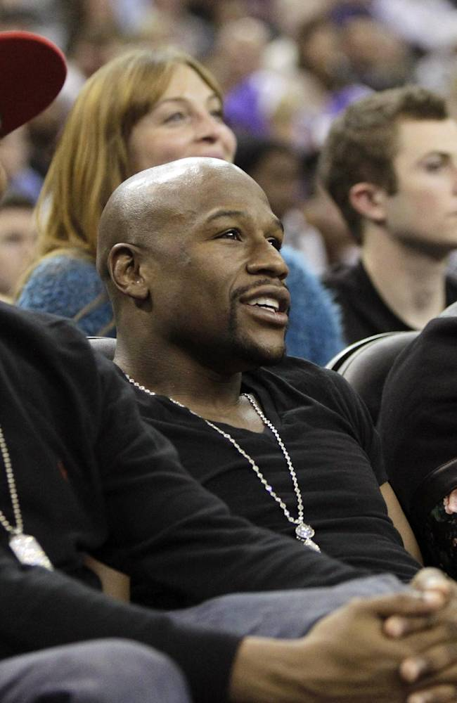 Boxing champ Floyd Mayweather, center, sits court side during the Sacramento Kings' 112-97 win over the Dallas Mavericks in a NBA basketball game in Sacramento, Calif., Monday, Dec. 9, 2013