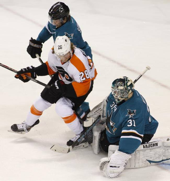 Philadelphia Flyers' Claude Giroux (28) and San Jose Sharks' Brad Stuart struggle for the puck in front of Sharks goalie Antti Niemi (31) during the second period of an NHL hockey game, Monday, Feb. 3, 2014, in San Jose, Calif