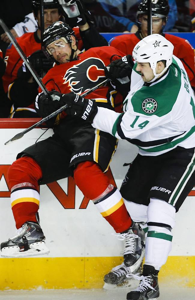 Dallas Stars' Jamie Benn, right, checks Calgary Flames' Chris Butler during the third period of an NHL hockey game in Calgary, Alberta, Thursday, Nov. 14, 2013. The Stars won 7-3