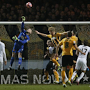 Manchester United's goalkeeper David De Gea punches the ball clear after a free kick by Cambridge United's Tom Champion, No 8, during their English FA Cup fourth round soccer match between Cambridge United and Manchester United, in Cambridge, England, Fr